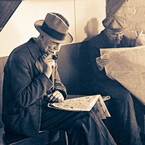 A photo of two men reading the news paper