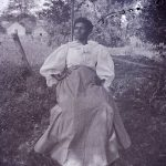 Portrait of older black woman sitting in a chair under a tree, early 20th century