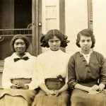 Photo of three young African American women sitting on the steps of a porch, 1920s